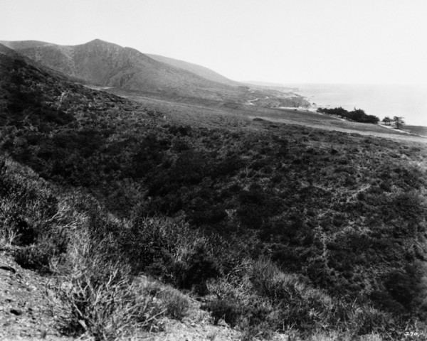 Between 1903 and 1910 Blanche Dolph held a partial interest in the area known as Coast Royal, seen here, left, near Camel Point south of Aliso Canyon. Joe Skidmore developed the property in the 1920s, as is evident from the water line. Aliso Peak, visible in the upper right of the picture, also is the highpoint in the photo on the left. This pre-1926 image looks south to Aliso Canyon from what is now called Hobo-Aliso Ridge, property also once owned by the Dolph sisters. The Monterey cypresses were planted along the old Coast Road, which served as primitive access before the 1926 construction of Coast Highway. First American Title Corporation Historical Photo Collection