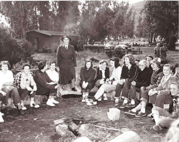 Olave Lady Baden Powell (1889-1977), standing, one of the founders of the Girl Scouts in Britain, visited Laguna's scouts at Aliso Canyon's Camp Elizabeth Dolph on one of her tours of scout groups, this one believed to be August, 1959. Susan Sizemore, with striped sleeve, could identify some fellow fifth- or sixth-grade scouts from Aliso and El Morro schools. To her right are Barbara Vanderbelt, Helen Starkweather, an unknown girl and Debbie Paul. Peering over Vanderbelt was Candy Vartasian. The other girls are not identified.