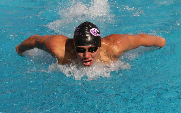 Senior Nile Koegel wins in the 100-meter butterfly with a time of 1:00.46.