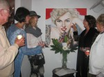 Artist-gallery owner Alexi Allens explains the details of her Marilyn Monroe  painting to art lovers and collectors at the gallery's opening during last week's Artwalk.
