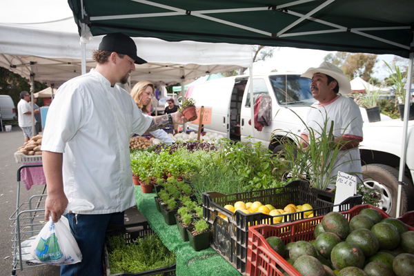 Chef Ryan Adams selecting produce at Laguna's farmers' market, which will relocate temporarily. Photo by Jodi Tiongco.
