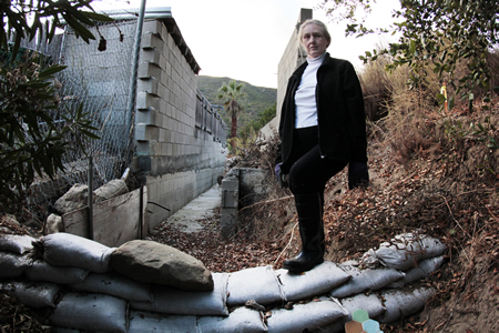 Silk artist Olivia Batchelder in the ravine that channeled floodwaters laden with broken glass into Sun Valley Drive houses, including hers, last December. A more substantial replacement to sand bags was approved this week to protect the neighborhood.