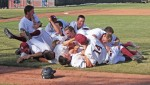 The baseball teams triumphant pile up.