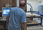 Production coordinator Bob Phillips watches as a computer-driven saw cuts perfect symmetrical and identical skimboard blanks from a sheet of plywood for a beginner line of boards.