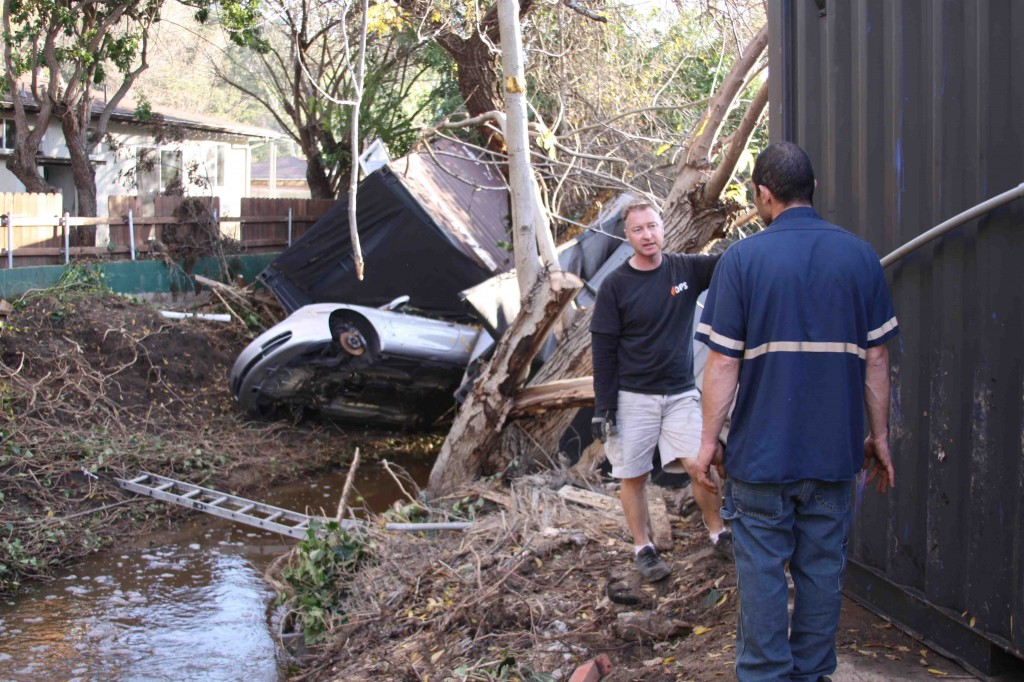 Canyon Road resident Jerry Moushey spoke this week with a tow-truck driver about extracting toppled containers from the creek. Photo by Andrea Adelson