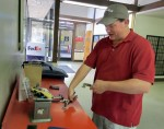 Chad Carter uses the post office scale to weigh his son's Pinewood Derby entry to ensure it stays under the 5 oz. limit. Isaac Carter's car was the Red Baron.