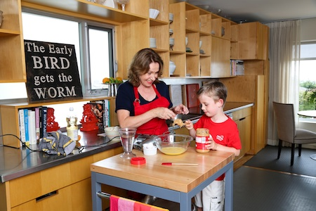 Lucy Mercer, baking doggie treats here with neighbor Luke, has published a cookbook compiled while teaching poor moms to create meals for their toddlers. Photo by Jody Tiongco