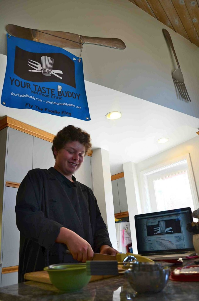 Noah Rosen, an almost ninth-grade freshman and food critic, chops homegrown basil in his own kitchen below a school project poster. His critique of cafeteria food stirred up a tempest among school administrators.
