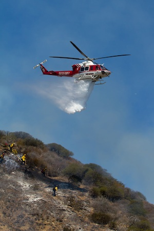 A water-dropping helicopter maneuvered within yards of hot spots, drenching flames with precision near Laguna Terrace Park on Sept. 20, 2012. Photo by Brian Guth