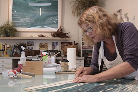 Printmaker Sheryl Seltzer adds more texture to a seascape woodcut.