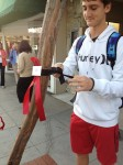 Student Nicholas Reikoff tied remembrance ribbons and names around downtown trees this past week. Photo by Justin Swanson