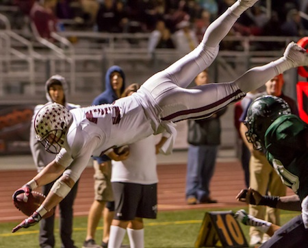 Hello! Drake Martinez leaps over Costa Mesa's Kurt Williams to score Laguna's third touchdown in the first half.