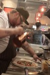 Chef Frank Deloach finishes off a thin-crust pizza that can cook in 90 seconds in Nea's wood-fired oven.