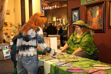 Celtic art therapist Erin Rado shares the therapeutic benefits of her creations with a visitor. She withdrew from the festival amid controversy over complying with manufacturing rules.