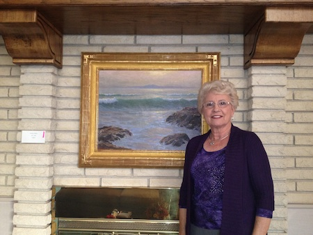 "Museum supporter Yvonne Boseker at home with artist Frank Cuprien's ""Laguna.""  Photo courtesy of Laguna Art Museum."