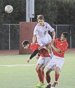 Sophomore Willy Wheeler goes up for a header between two Oxford Academy players.