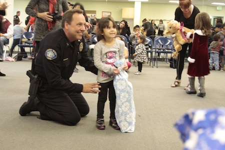 Local resident Chloe Estrada, 4, in her first year at the club, poses with a police officer with her new blanket.