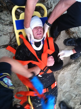 Paramedics tend to Neal Hruby at Agate Street Beach after he slammed into a submerged rock and was pulled unconscious from the water.