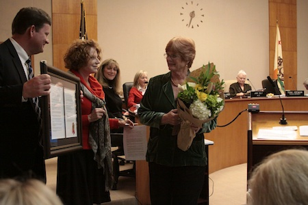 John Pietig, left, and Council member Toni Iseman, center, present a plaque to former Council member Verna Rollinger last December.