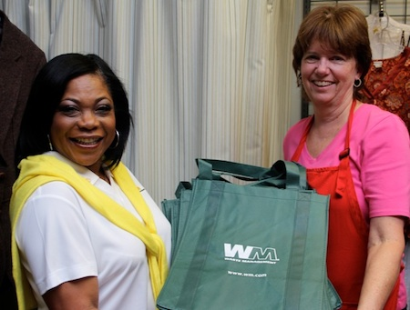 Michelle Clark, left, provides Janene Freitas reusable bags for Assistance League customers without their own.