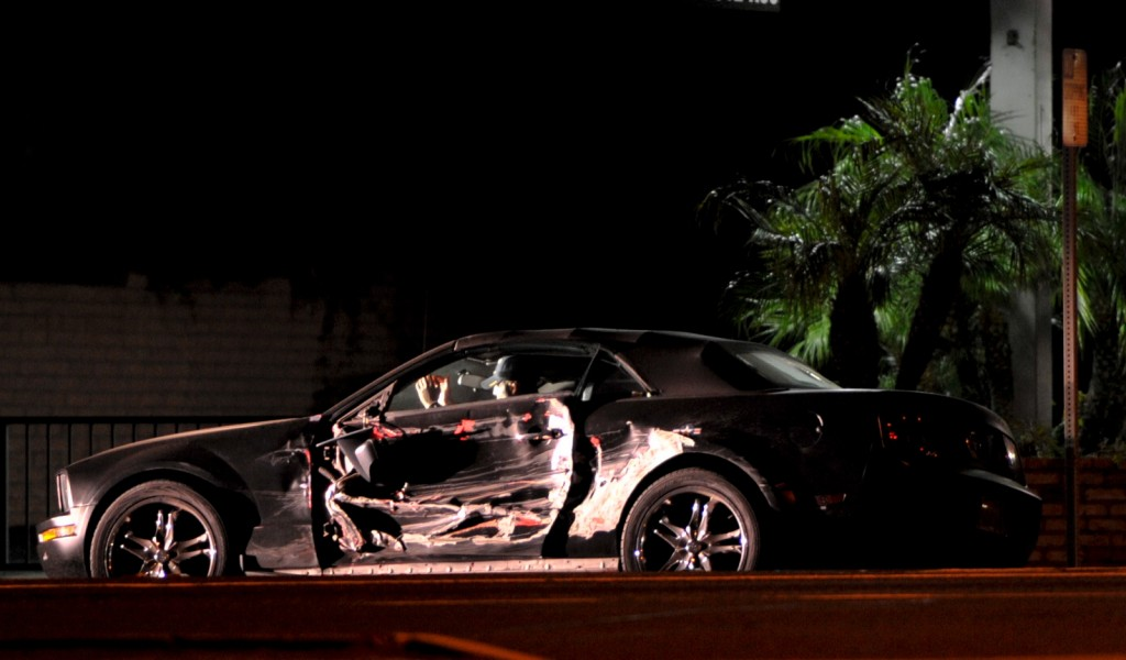 The suspected gunman in his battered car with his hands raised at the direction of police. Photos by Craig Miller