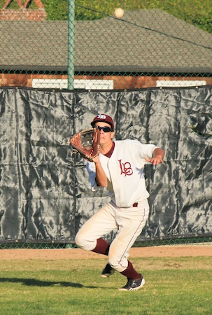 Senior left fielder Kaito Lee battles the late afternoon sun to haul in a fly ball in the Laguna's 11-2 win over Jurupa in the opening game of the Newport Elks Tournament at Skipper Carrillo Field.