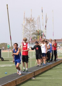 Pole vaulters wait their turn at a practice run before.