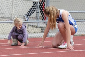 The daughter of Laguna girls' Coach Steve Lalim receives some pointers on her form from a Dana Hills runner.