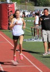Janie Crawford wins the 800 at the Godinez dual meet while Coach Steve Lalim looks on with stopwatch in hand.