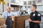 Officer Darrel Short, assigned to foot patrol downtown, hears out merchant Luke Solis.