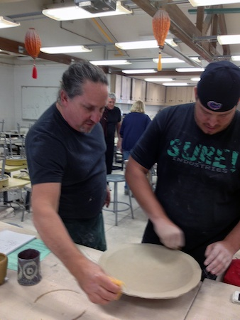 Ceramics Prof. Steve Dilley lends a hand.