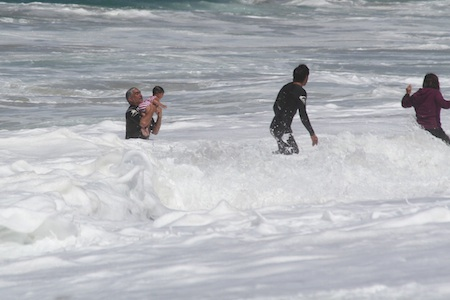 Pat Watson, left, holds an unidentified child he pulled from the whitewater at Aliso Beach on Saturday.