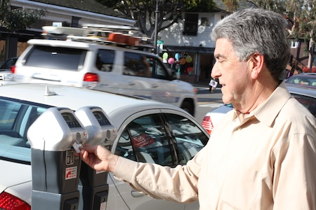 Norm Grossman, who survived dissent over his re-appointment to the Planning Commission last week, tries out a smart meter, whose new features may help solve parking problems downtown. Photo by Edgar Obrand