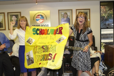 School Power's Robin Rounaghi cheers on third grade teacher Mary Minerman, recipient of an $800 grant to bolster TOW classroom libraries.