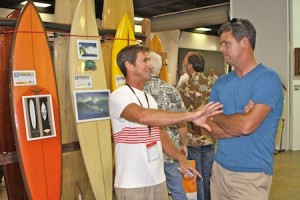 "Photo by Jim Collins Robert ""Wingnut"" Weaver, left; with Peter Mel, winner of the invitation only Mavericks Surf Contest held in January, alongside a few of the many surf boards sold at auction."