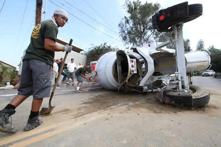 Workers cut open the drum of a downed cement truck on Monday in order to empty the barrel and pull the rig upright.