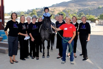 Shea volunteer Sandy White holds Bliss, ridden by Nikolai Amy, along with league members, from left; Elaine Merz, Ann Hyde, Joan Kasman, Judy Soulakis, Linda Hall, Gayle Whitaker, Karen Mauro, Ginny Skelton and Jacinta Loewen.