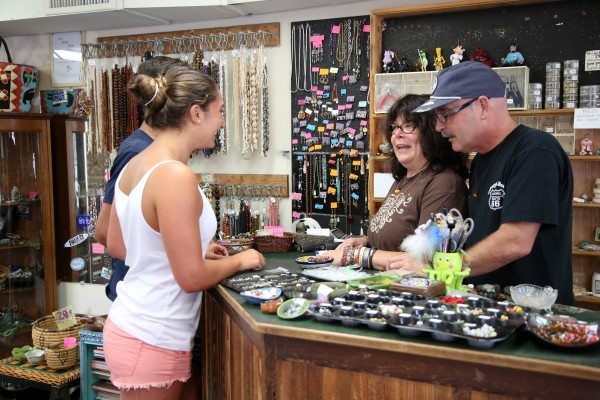 Bead Shop owner Peggy Smith, along with her husband George Harney, here helping customers, are selling a store with a long history.