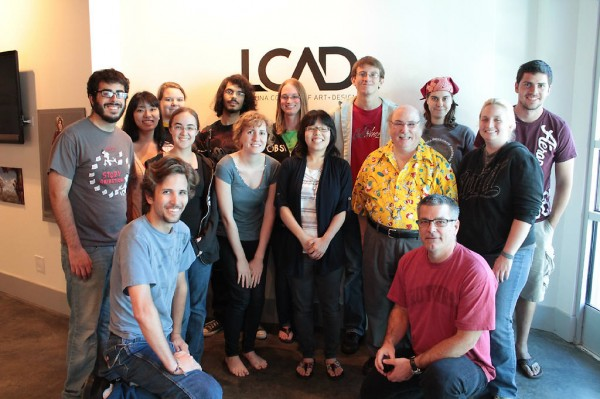 Students surround legendary Disney animator, director and voice actor Eric Goldberg, standing.