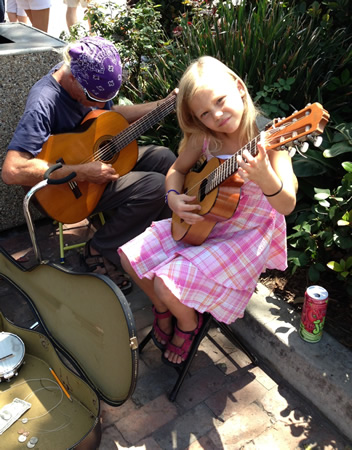Finger-picking guitarist Tomi, 7, and her father, Hemet glass artist Tom Licon, weekend street buskers on Forest Avenue, will perform in Saturday's free concert downtown.