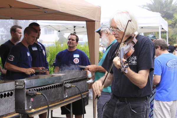 Artist-violinist Doug Miller entertains firefighters pouring batter and frying sausages as well as patrons of the fog-shrouded Exchange Club fundraiser in Heisler Park this past Monday, Sept. 2.