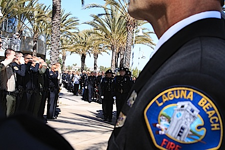 Scores of uniformed officers saluted their colleagues as Jon Coutchie's casket was walked into Mariners Church in Irvine.