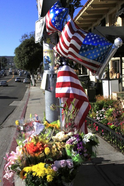 Flowers and flags mark the intersection of a fatal collision where Officer Jon Coutchie was killed.