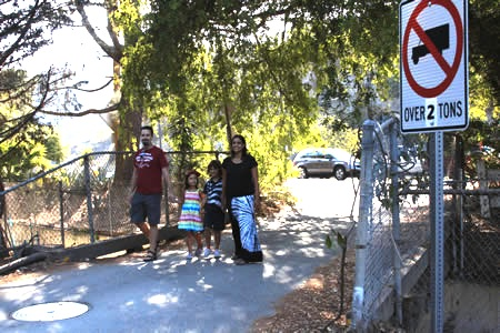 Thurston Park residents Craig O'Neill and Peri Doshi-O'Neill and their children cross the deteriorating Milligan Drive bridge.