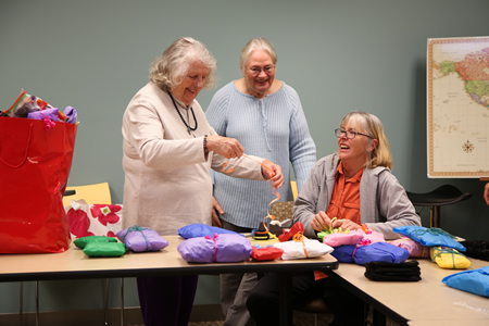 From left, guild members Maria Martini, Yves Newman and Roberta Luque finish up their packaging.