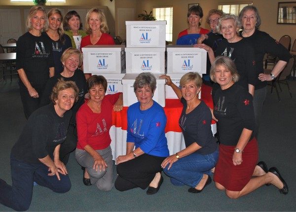 Assistance League Board members and boxes of donated books. From left to right, Kneeling, from left to right: Jacinta Loewen, Karen Mauro, Gayle Rose, Judy Soulakis, Christine Montonna, and Gayle Whitaker. Standing, from left to right: Ann Hyde, Valerie Milan, Kathleen Hardcastle, Marcy Tillman, Janene Freitas, Diane Gelfer, Joan Kasman, and Mary Jane Yohe.