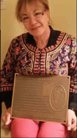 """Zahide Lawrence with a plaque designed by local Bill Atkins that will serve as a permanent memorial to her husband, Harry Lawrence, who earned the nickname """"Mr. Laguna."""""""