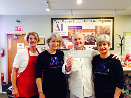 Second from right, Andy Siegenfeld, chair of the Laguna Food Pantry, receives a $4,100 check from Laguna Beach's Assistance League, including members, from left, Lynne Vihlene, Gayle Whitaker and Judy Soulakis.