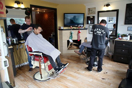 The Den's owner Brandon Ferguson attends to a patron of his retro barbershop and shave parlor and adds to the character of Laguna's newest retail section, the Pearl Street District