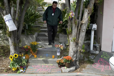 A public administrator  threads through the informal shrine outside Nicholson's home in 2009.